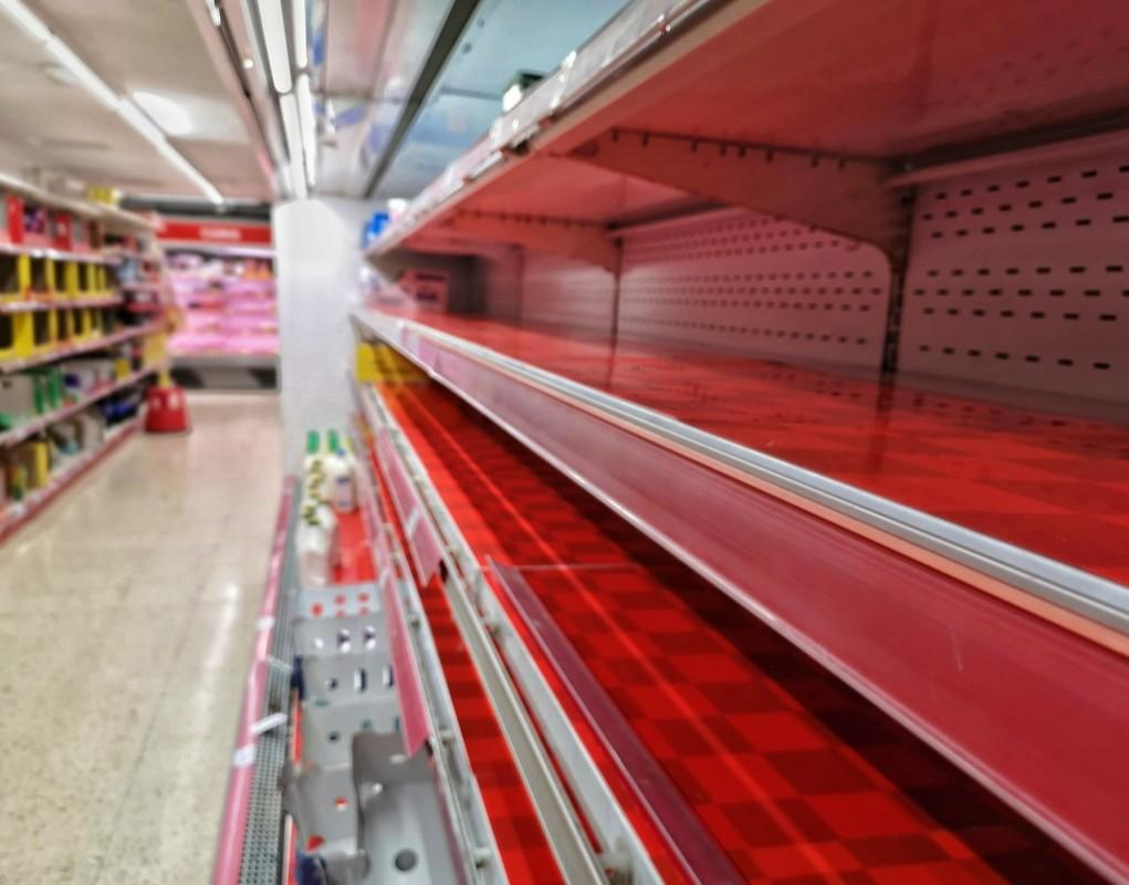 A row of empty shelves in a supermarket during COVID-19