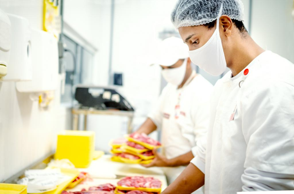 A man wearing a hairnet and mask handles raw meat in a brightly lit facility