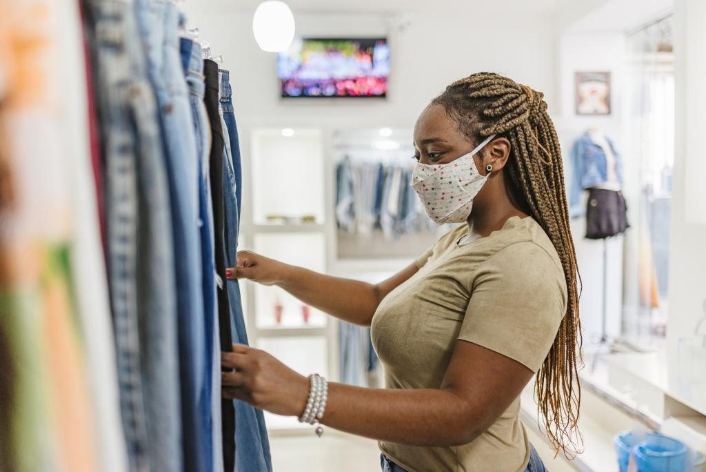 A young woman browses a row of jeans in a store while wearing a face mask