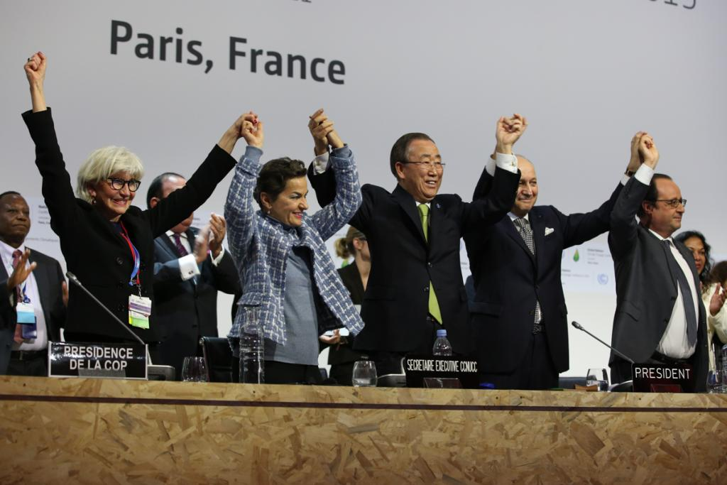 Country delegates raise joined hands to celebrate the signing of the Paris Agreement at the United Nations