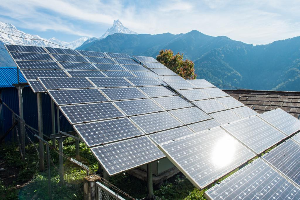 Solar panels in a field with mountains in the background