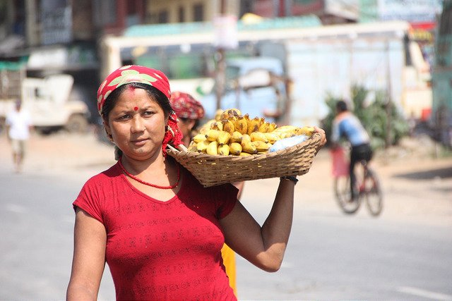 Nepalese woman in red top carrying a basket of banana