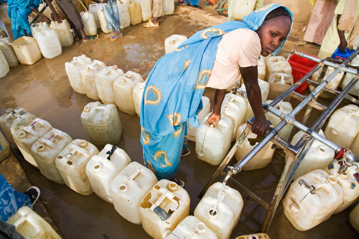 Woman at a water point in Sudan picking up canisters of water