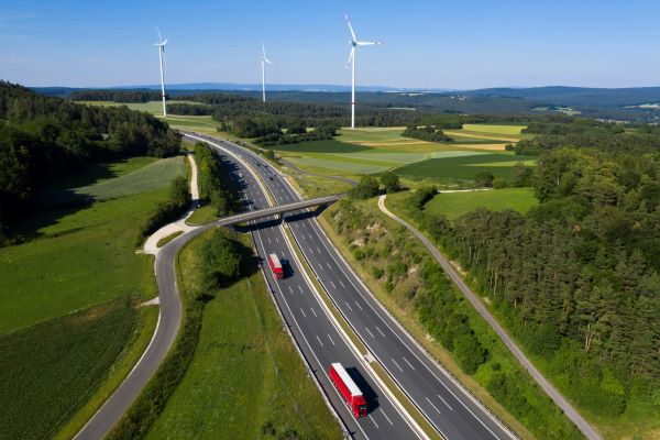 Aerial view of highway in England on a sunny day with green hills and wind turbines