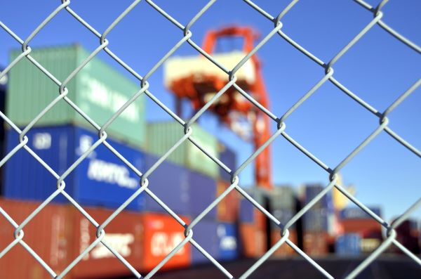 Shipping containers behind a chain-link fence during the day for story about the USMCA