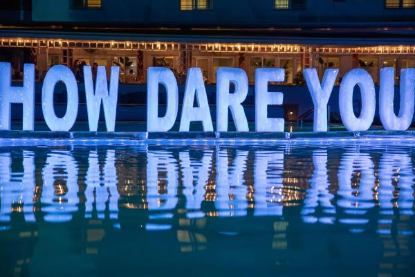 "Melting ice sculpture of the words ""How Dare You"" by Rubem Robiard, example of climate art"