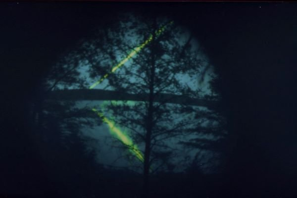 Dark image of lake and trees with beam of green light