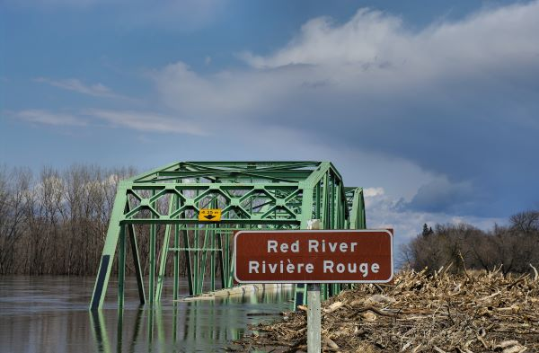 Flooded Red River in Manitoba with bridge in background for story on COVID-19 and how to prepare for crisis