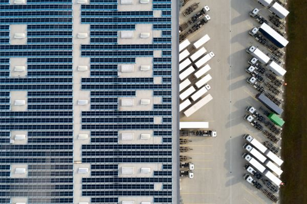 Aerial view of solar panels on a warehouse roof with trucks parked next to it