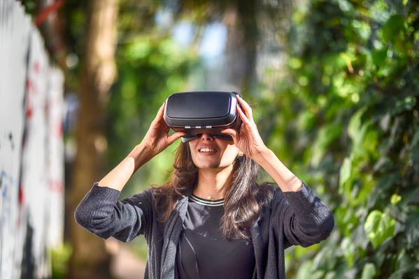 Woman wearing virtual reality glasses outside