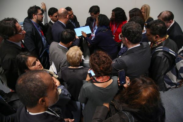 Delegates huddle in a hallways at COP 25 in Madrid in 2019; summits like these have been canceled or postponed since COVID-19