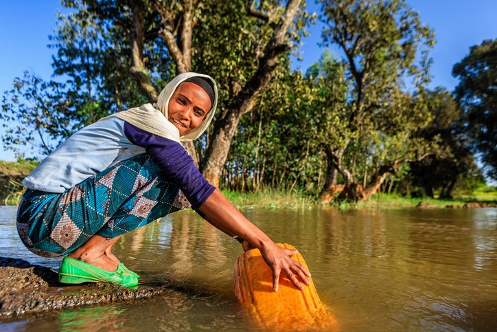Woman taking water out of a river in Ethiopia