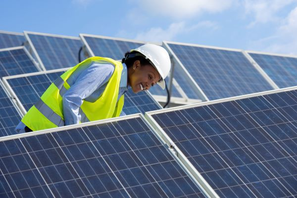 A black woman in a neon construction vest smiles while inspecting solar panels on a sunny day