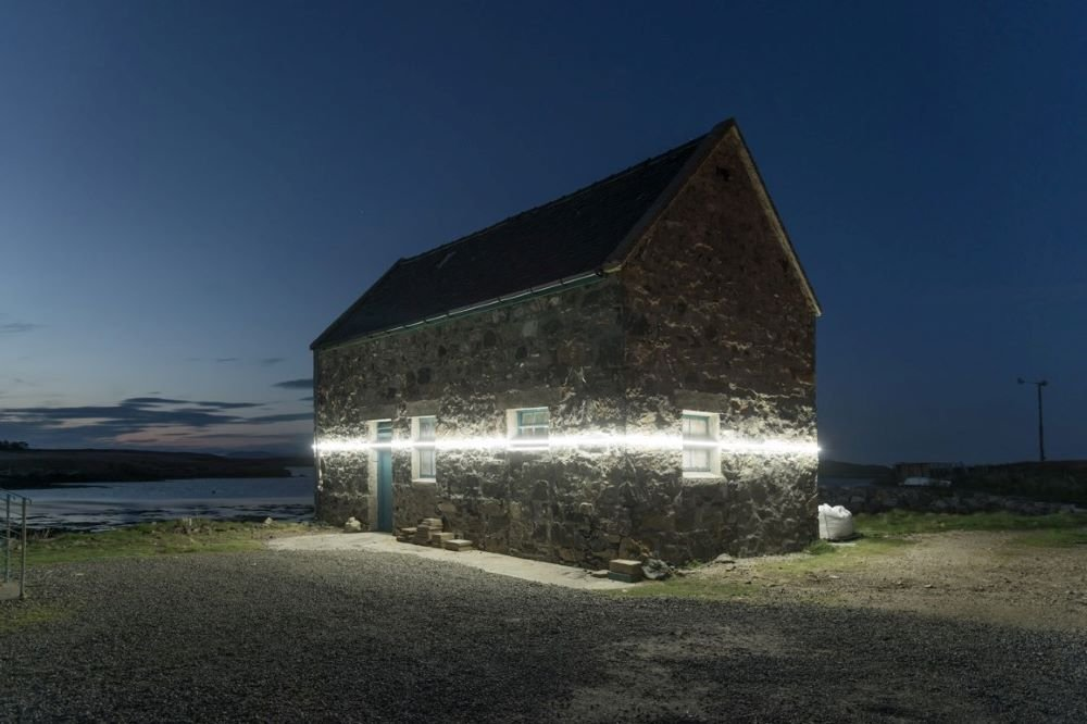 Climate art: Photo of a beam of light on a stone house at night in Scotland