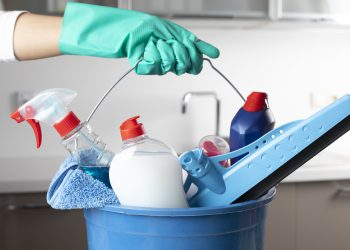Gloved hand holding blue bucket full of detergents and cleaning materials
