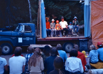 Group of people with back to camera watch people on a stage on a trailer sitting in a straight line