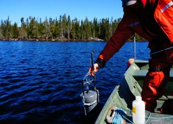 Scientists in orange suit lowers tank into bright blue freshwater lake