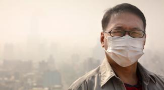 A closeup of a man wearing a cloth mask covering his nose and mouth in the foreground of a dusty landscape.
