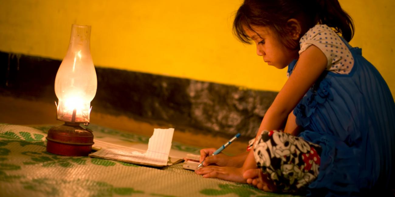 A young girl sits by a lamp on the floor writing on a piece of paper.