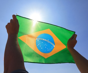 Brazil flag in hand with sky and sun